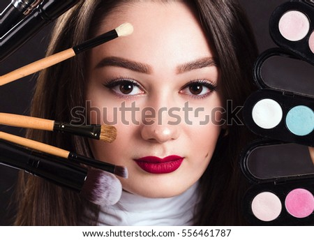 The face of a beautiful girl with brushes for make-up and eye shadow on a black background