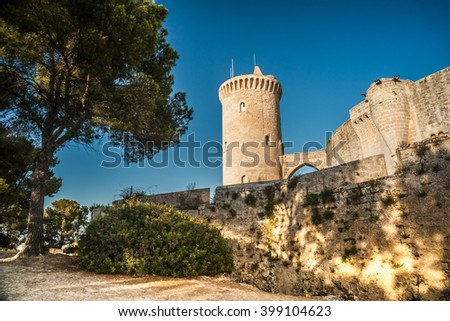 The famous Bellver Castle fortress in beautiful sunset light against blue sky, in Palma-de-Mallorca, Spain. Travel destination, landmarks of Palma de Mallorca.