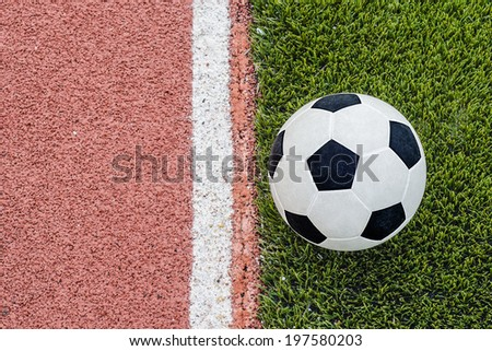 The football is near the line on the artificial grass soccer field in the stadium.