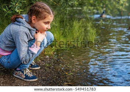 The girl-child near the pond. A child near water.