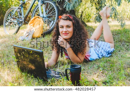 the girl has arrived by bicycle to park, has sat down under a tree to have rest. in hands a  camera roll