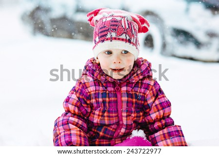 the girl in a lilac down-padded coat walks in snow weather on snowdrifts