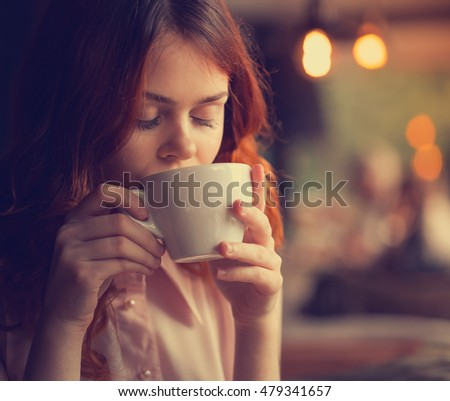 the girl in the cafe, a beautiful young woman in a cafe enjoying the taste of the drink