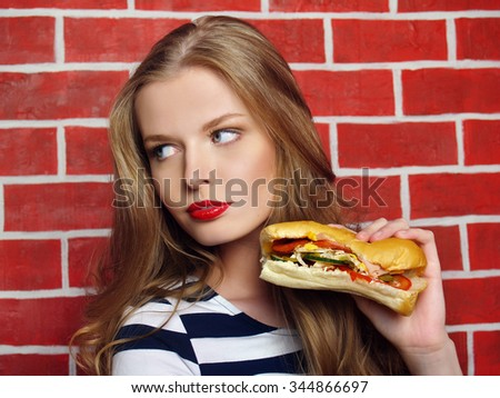 The girl in the restaurant with exposed brick walls keeps the sandwich