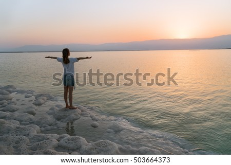 The girl on the shore of the Dead Sea in Israel at sunrise