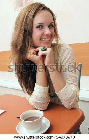 The girl sits in cafe at a table and smiles