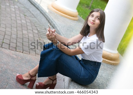 the girl sits in park near white columns with phone