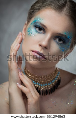 The girl with bright fashion make-up and sparkles