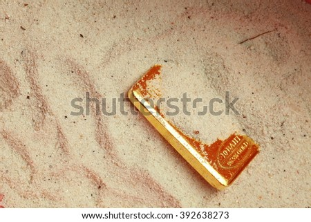 The gold bar put on the sand background represent treasure and business finance concept related idea.