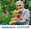 The grandfather sits on a lawn and holds the cheerful grand daughter on hands. - stock photo