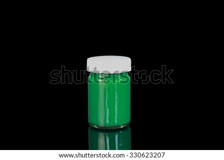The green color bottle in black background.