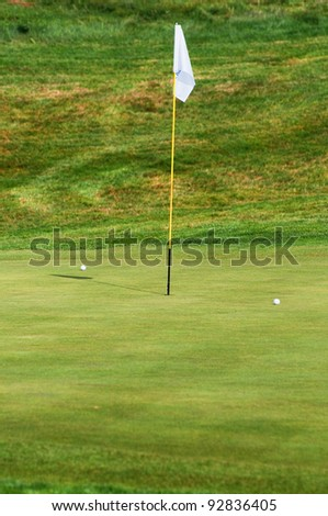 The green field, a flag and two golf balls