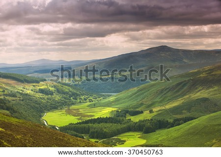 The green irish mountains with the rain clouds