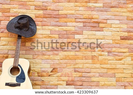 The guitar and cowboy hat on brick wall