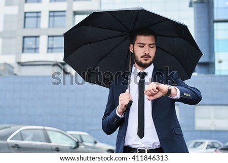 The guy in the suit on the Parking lot with an umbrella in the hands of your watch