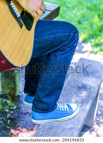 The guy playing guitar in park, outdoor