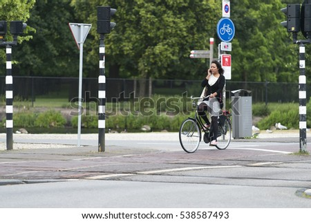 THE HAGUE, NETHERLANDS - JULY 8, 2015: A woman driving a bicycle, while talking with her mobile phone.
