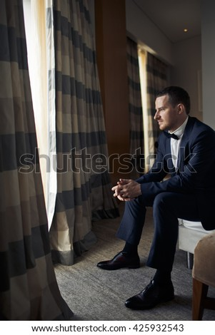 The handsome groom sits near window