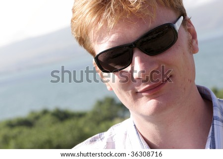 The happy red-haired man poses outdoor in summer