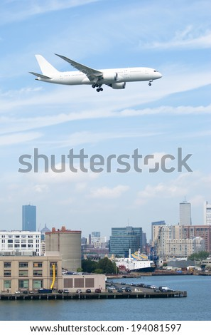 The huge plane is flying over Boston downtown towards the airport (Massachusetts).