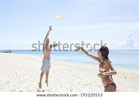 the image of couple playing Frisbee on the beach