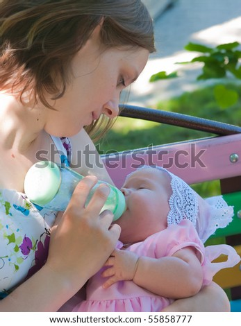 The image of the woman feeding the daughter from a children's small bottle