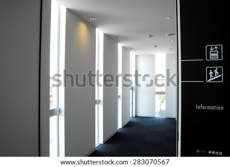 The interior decoration of a building based on white and black. The guidance indication of an elevator and stairs.