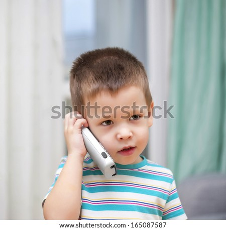 the kid speaks by phone at home