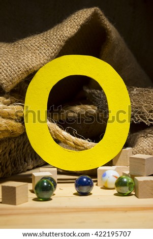 "The letter "" O "" by  Photo font "" Yellow Texture "" and subjects with active texture. Wood, burlap, glass beads. Preparation for graphic design"