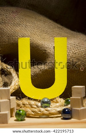 "The letter "" U "" by  Photo font "" Yellow Texture "" and subjects with active texture. Wood, burlap, glass beads. Preparation for graphic design"