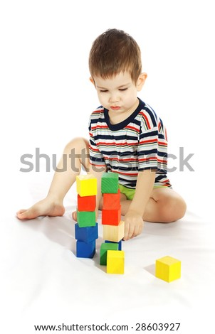 The little boy plays with cubes