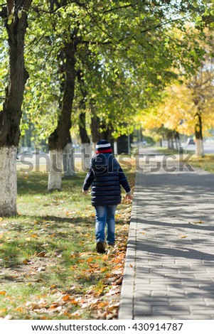 the little boy walks on the autumn city with yellow leaves