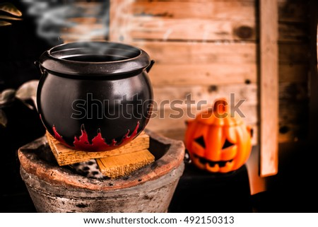 The magic Witch's cauldron potion conjures in the wizarding lair. Halloween pumpkin head on wooden background