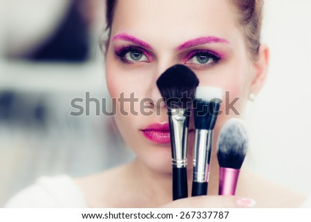 The makeup artist with bright pink make-up holds powder brushes. She covers with them the face. Studio portrait.