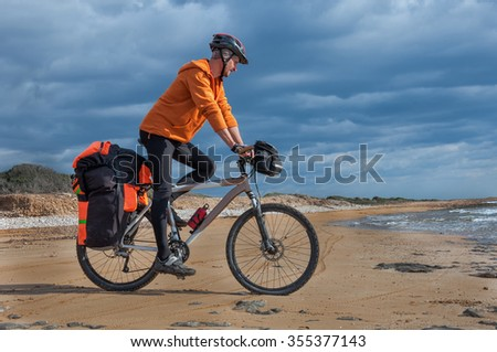 The man goes on a sandy beach on a mountain bike with a big backpack. Cyprus