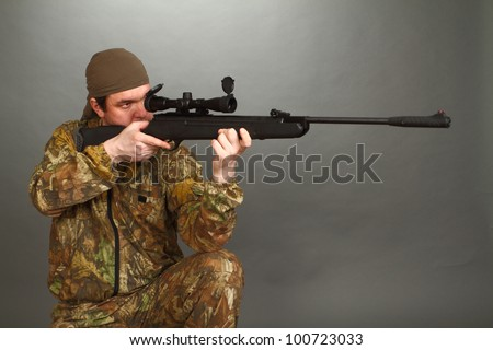 the man in a camouflage aims from a rifle with a riflescope