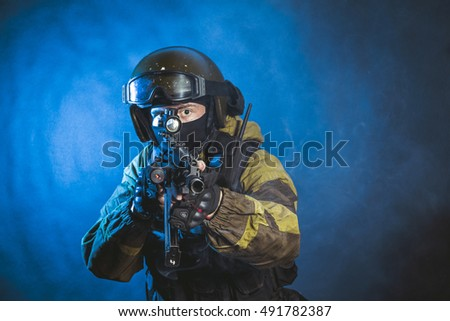 The man in the image of a member of the special forces division with assault rifle in blue light. Russian police special force - Special Rapid Response Unit or SOBR (Spetsnaz).