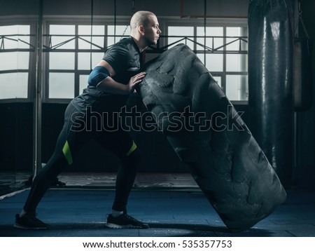 The man turns the tire, crossfit functional sport. Young guy exercising with a wheel sports functional training in the gym.