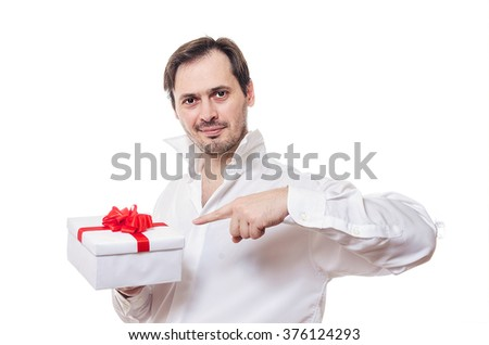 The man with a bristle in a white shirt points a finger at a gift in a white box with a red bow