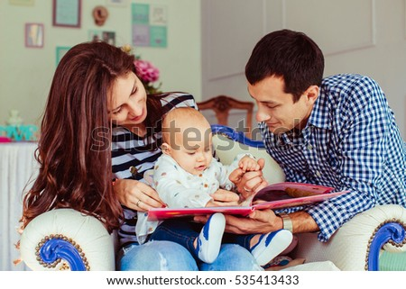 The mother, father  and  daughter reading a book