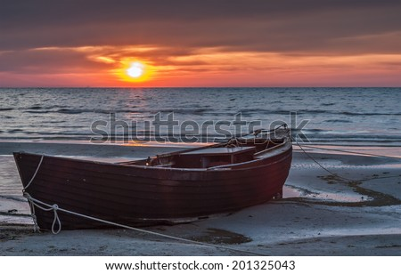 The old fishing boat at the early morning on sandy beach of the Baltic Sea, Latvia, Europe
