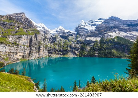 The panorama in summer view over the Oeschinensee (Oeschinen lake) and the alps on the other side near Kandersteg on bernese oberland in Switzerland.
