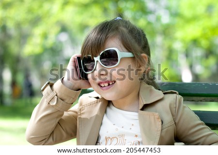 The park Smiling little girl with glasses talking on cell phone