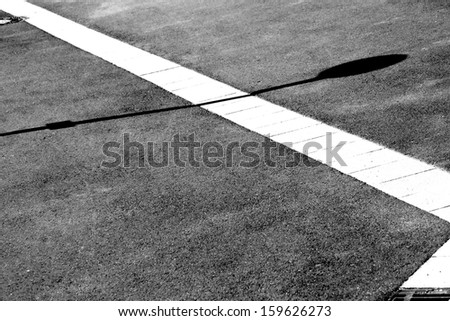The photograph of a sidewalk in the sunlight with Gully drains and shadows / Sidewalk top view