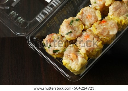 The pork dumpling in clear plastic tray packaging put on dark background scene.