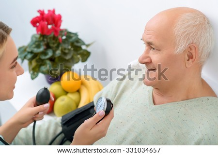 The pressure is fine. Smiling senior aged man finds out that his heart works better and his visitor is more than happy to announce it.