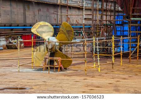 The propeller of a vessel in a dry dock being prepared for maintenance works.