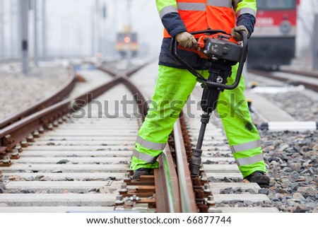 the railroad worker fixes a screw on the rails
