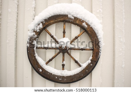 The ship wheel on the wall covered with snow . Winter scene.