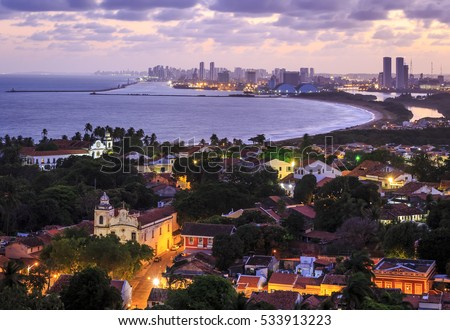 The skyline of Olinda and Recife in Pernambuco, Brazil contrasting the historic buildings of Olinda dated from the 17th century with the contemporary skyscrapers of Recife at sunset.